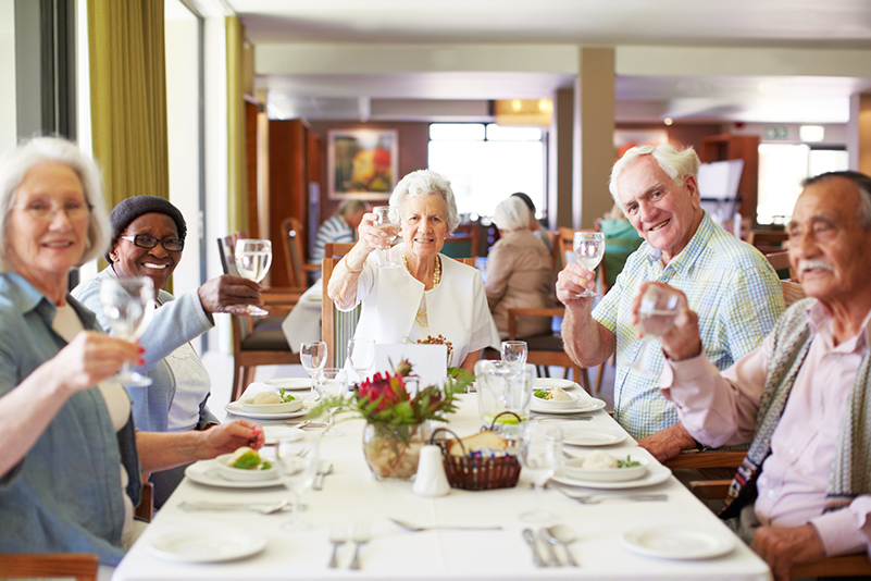 A group of seniors raising their glasses during a meal at a senior living community.