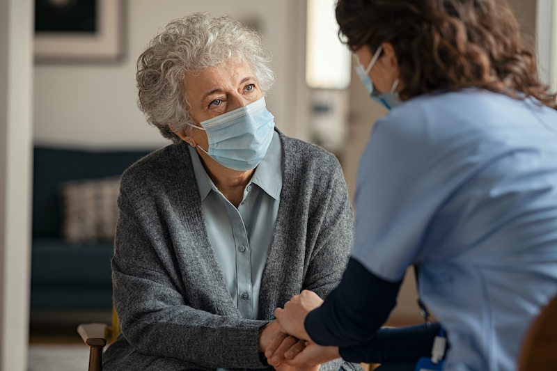 Doctor treating a senior wearing a face mask during visit