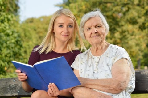 A woman shares a book with an elderly person in her care.