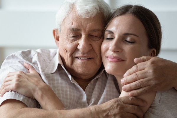 A woman comforts her aging father.